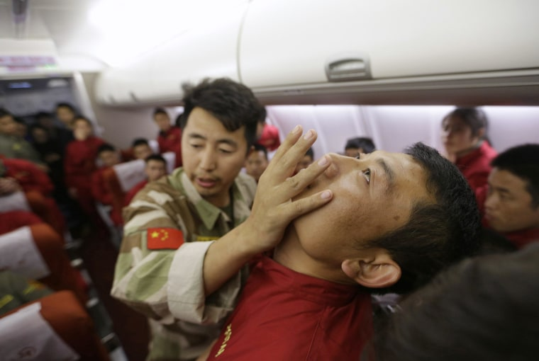 Image: An instructor pushes a student's jaw during a special course on flight safety on the outskirts of Beijing