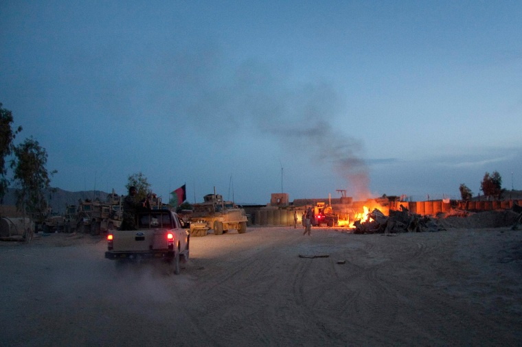 Image: An Afghan National Army pickup truck passes parked U.S. armored military vehicles, as smoke rises from a fire in a trash burn pit at Forward Operating Base Caferetta Nawzad, Helmand province south of Kabul, Afghanistan