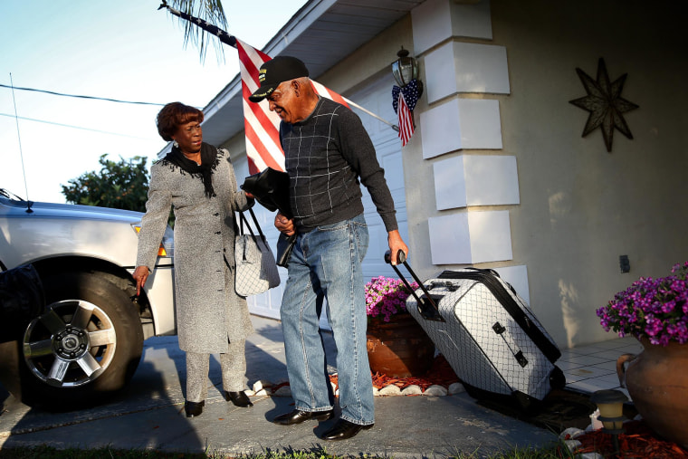 Image: U.S. Army Staff Sergeant Melvin Morris, a Vietnam War veteran, and his wife, Mary Morris, leave their house on their way to Washington, DC