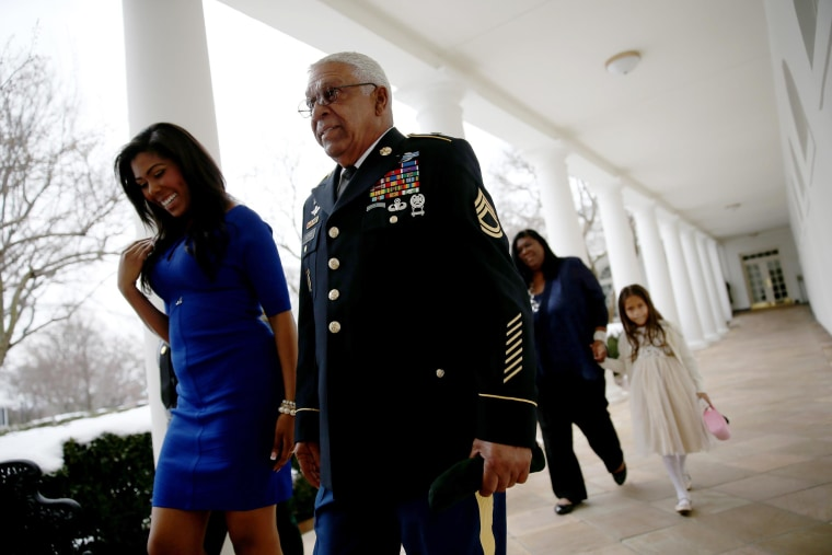 Image: U.S. Army Staff Sgt. (Ret.) Melvin Morris,  a Vietnam War veteran, walks with his granddaughter,  Symone Barnes, after they met President Barack Obama in the Oval Office and before a ceremony to award him the Medal of Honor