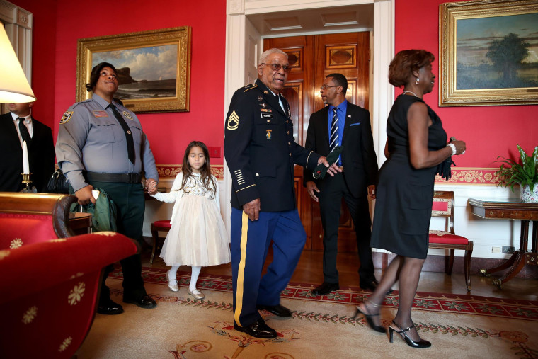 Image: U.S. Army Staff Sgt. Melvin Morris, a Vietnam War veteran, center, walks with his family before a ceremony to receive the Medal of Honor in the White House
