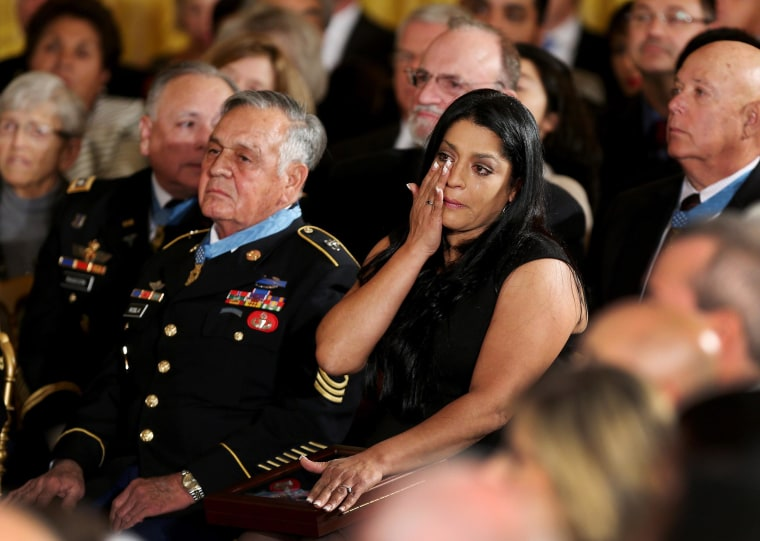 Image: Medal of Honor recipient U.S. Army Sgt. First Class (Ret.) Jose Rodela, left, a Vietnam War veteran, sits next to Lenora Alvarado who wipes away tears after accepting the Medal of Honor on behalf of her father, Vietnam War veteran Specialist Four L