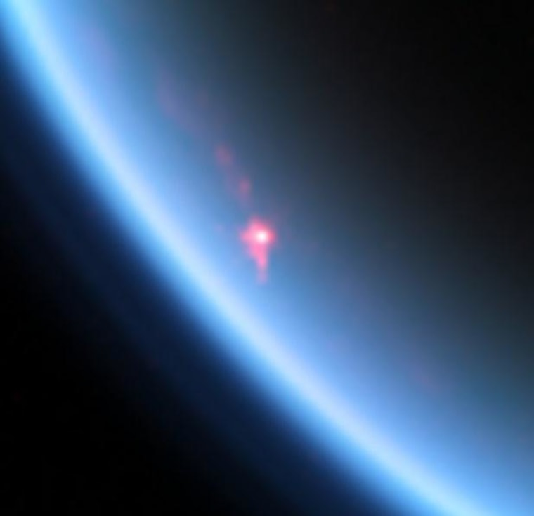 An image from the Cassini probe's Visual and Infrared Mapping Spectrometer shows the glint of sunlight reflected by hydrocarbon lakes on Titan, one of Saturn's moons.