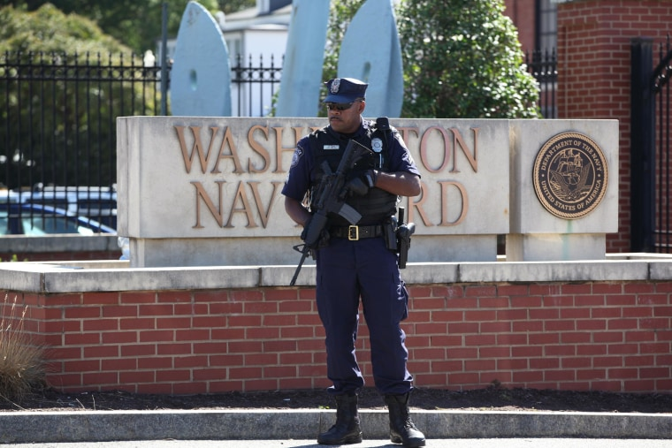 Image: A Navy employee who did not want to be identified lays flowers near the main gate to the Washington Navy Yard.