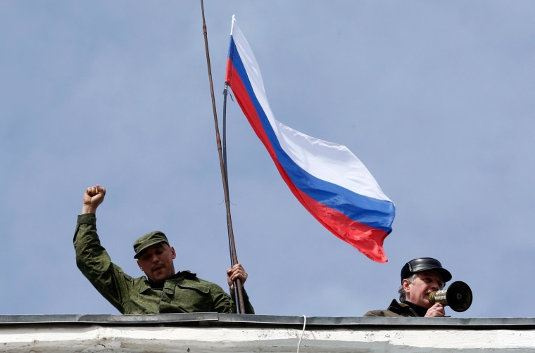 Image: A man holds a Russian flag on the roof of the naval headquarters in Sevastopol