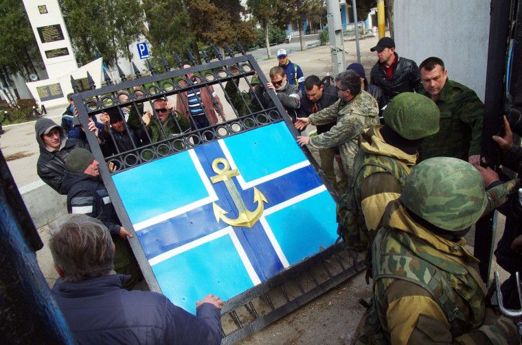 Image: Pro-Russian protesters remove the gate of Ukrainian navy headquarters as Russian troops stand guard