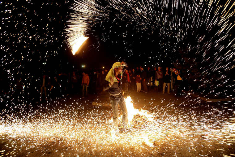 "An Iranian man lights fireworks during a celebration known as ""Chaharshanbe Suri,"" or Red Wednesday, marking the eve of the last Wednesday of the solar Persian year, in Pardisan Park, Tehran on Tuesday."