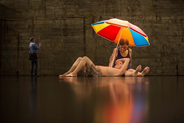 A man photographs a sculpture entitled 'Couple under an Umbrella' by Australian artist Ron Mueck during the opening day of his exhibition at the Museum of Modern Art in Rio de Janeiro, Brazil, on March 19. The exhibition will run up to June 1, 2014.