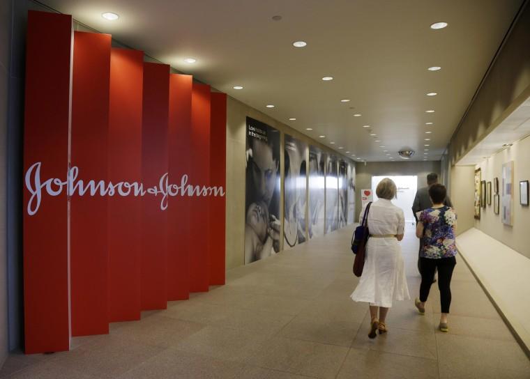People walk along a corridor at the headquarters of Johnson & Johnson in New Brunswick, N.J.