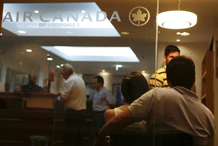 Image: Customers wait their turn to be served at the Air Canada's office in Caracas