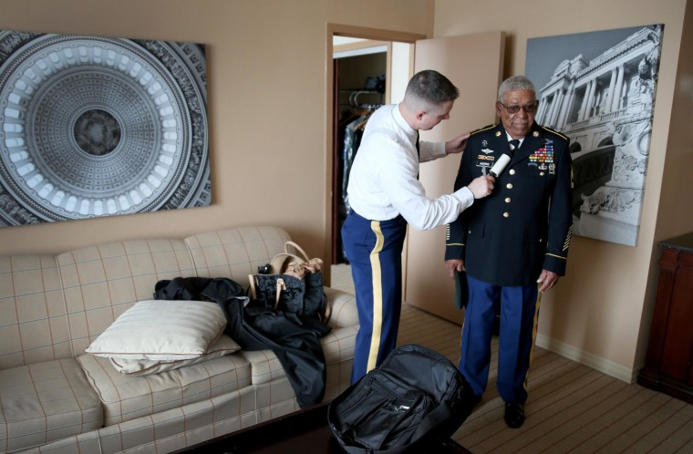 Image: U.S. Army Staff Sergeant Christopher Schneider uses a lint roller on the uniform of U.S. Army Staff Sgt. (Ret.) Melvin Morris, right, a Vietnam War veteran, as they prepare to make their to the White House