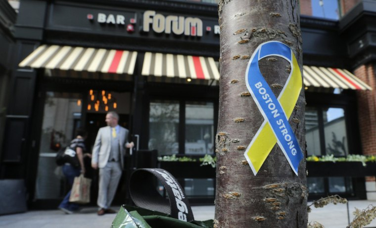 "A ""Boston Strong"" sticker is stuck to the trunk of a tree as a manager opens the door for a worker outside the Forum restaurant and bar near the finish line of the Boston Marathon, in Boston, on Aug. 15, 2013.  The restaurant, which was damaged after one of the bombs exploded in front of the building, reopened Thursday, for a private event, for the first time since the race."