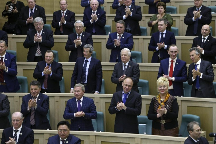 Image: Members of the Federation Council, Russia's upper house of parliament, applaud during a session in Moscow