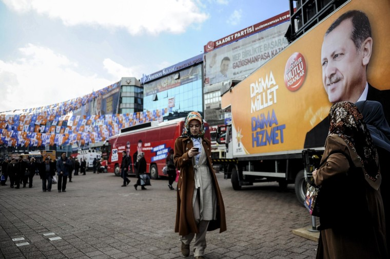 A woman looks at her smartphone in front of a banner displaying a portrait of Turkish prime minister Recep Tayyip Erdogan in Istanbul on March 21, 2014.