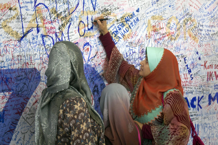 People writing messages for the passengers aboard missing Malaysia Airlines flight MH370 at the international airport in Kuala Lumpur.