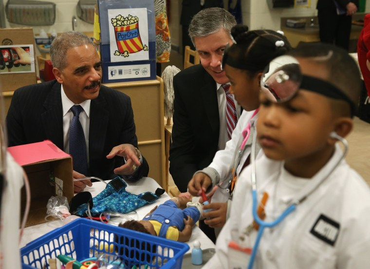 Image: Eric Holder And Arne Duncan Visit Washington DC Elementary School