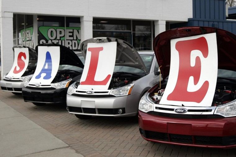 Image: Four 2009 Ford Focus vehicles sit with a 'Sale' sign under their hoods.