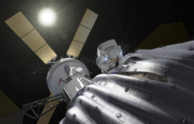 An artist's conception shows an astronaut preparing to take samples from a captured and bagged asteroid after it has been relocated to a stable orbit beyond the moon. An Orion crew spacecraft hangs in the background.