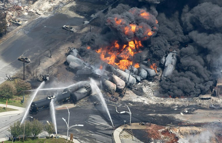 Image: Smoke rises from railway cars that were carrying crude oil