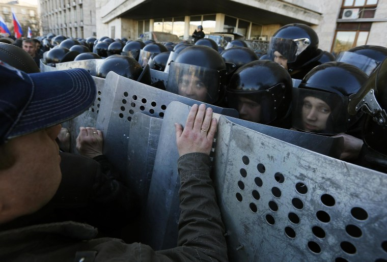 Image: Pro-Russian protesters push Ukrainian riot policemen guarding the regional administration building in central Donetsk
