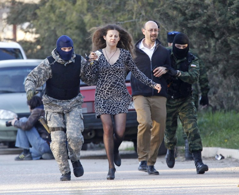 Image: Members of pro-Russian self-defence units run together with plain-clothes people outside a military base in the Crimean town of Belbek near Sevastopol