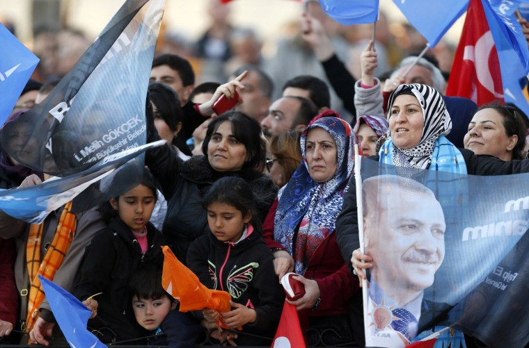 Image: Supporters of Turkey's Prime Minister Tayyip Erdogan wave his portraits and Turkish and his ruling Ak Party (AKP) flags during an election rally in Ankara