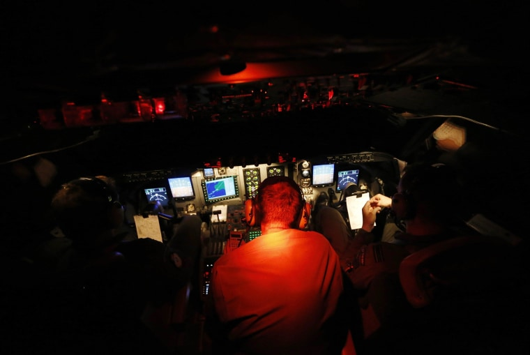 Image: Pilots and engineers sit in the dark cockpit of a Royal New Zealand Air Force P-3K2 Orion aircraft as they return at night from the search for missing Malaysian Airlines flight MH370