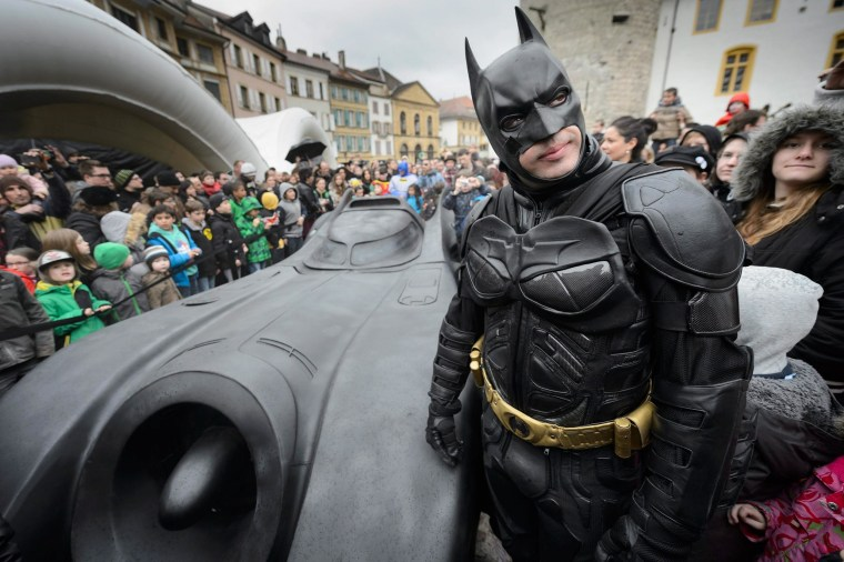 Image: A man disguised as Batman stands next to the Batmobile during the opening of the exhibition 'Superman, Batman & Co...mics' at the 'Maison d'Ailleurs' (lit: House of Elsewhere), museum