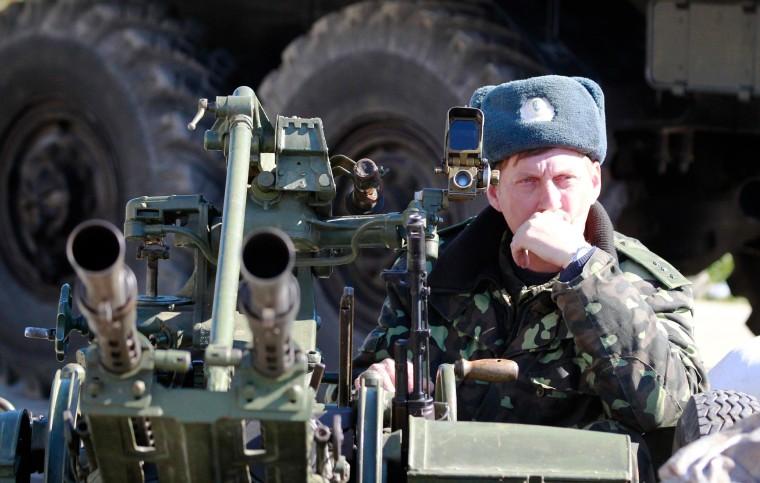 Image: A Ukrainian serviceman guards a military base in the Crimean town of Belbek near Sevastopol