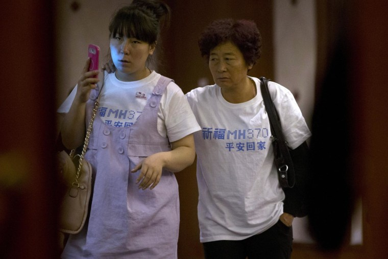 """Image: Relatives of Chinese passengers aboard the missing Malaysia Airlines, MH370, walk out from a meeting room in a hotel wearing a t-shirt which reads """"Pray for MH370 safe return"""" in Beijing, China"""