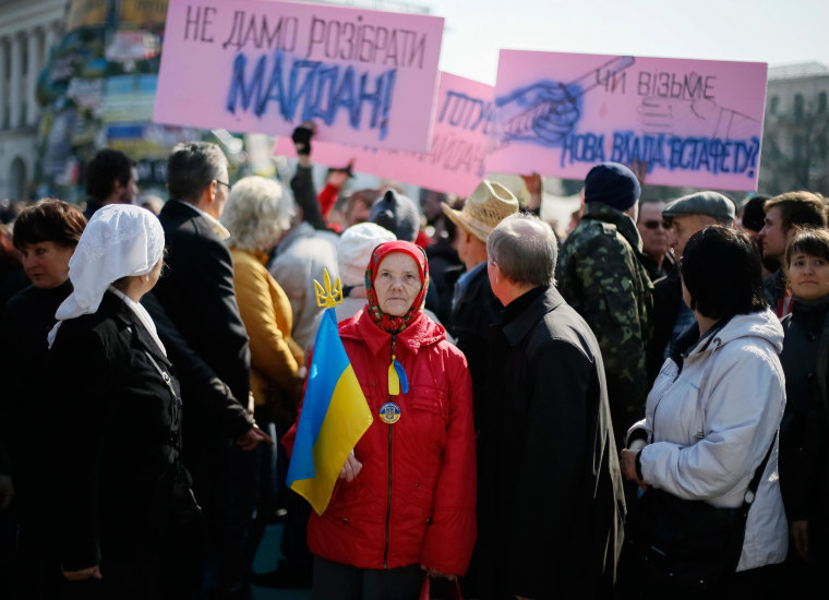 Image: A woman holds a Ukranian flag as she attends an anti-war rally at Independence Square in Kiev