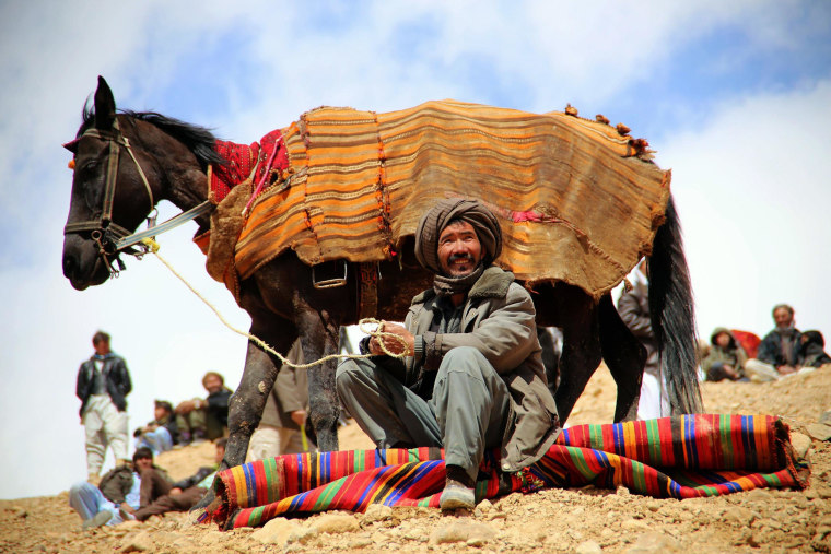 Image: An Afghan horseman looks on during a game of Buzkashi near Bamiyan city in central Afghanistan on March 23, 2014.