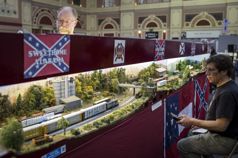 Image: A model railway enthusiast controls working model trains