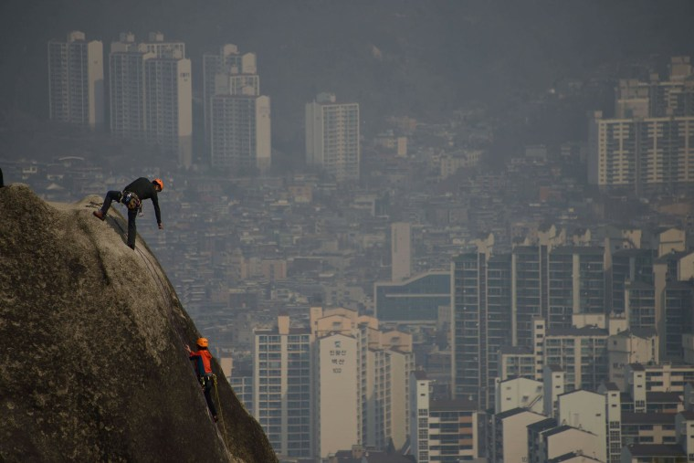 Image: Climbers scale a rock face as a think layer of pollution hangs over the Seoul skyline