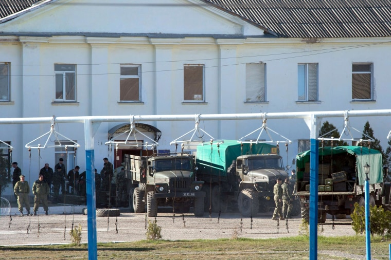Image: Ukrainian soldiers load weapons and ammunition into trucks in the Crimean city of Feodosia