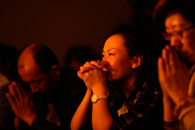 Image: Relatives of passengers onboard Malaysia Airlines Flight MH370 pray at a praying room at Lido Hotel in Beijing
