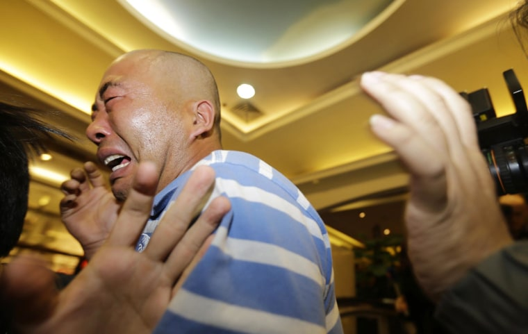 Image: Relatives of passengers aboard Malaysia Airlines MH370 cry after watching a television broadcast of a news conference, in the Lido hotel in Beijing