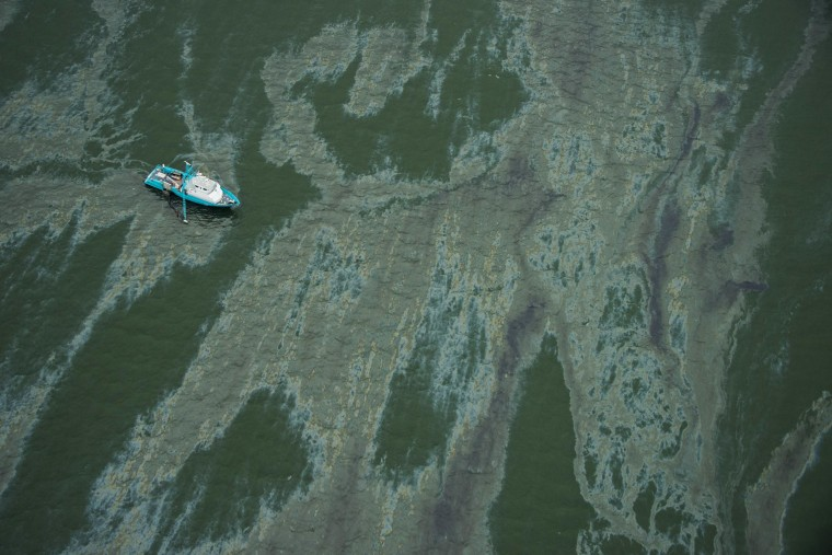A vessel surrounded by a sheen on the water near the Port of Galveston on Sunday, March 23, 2014, in Galveston, Texas. Dozens of ships are in evolved in clean-up efforts to remove oil that spilled into Galveston Bay after a ship and barge collided near the Texas City dike on Saturday afternoon. (AP Photo/ Houston Chronicle, Smiley N. Pool)