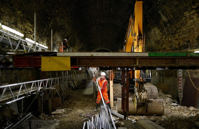Image: A worker dismantles scaffolding in the Connaught Tunnels section of the Crossrail construction project in East London