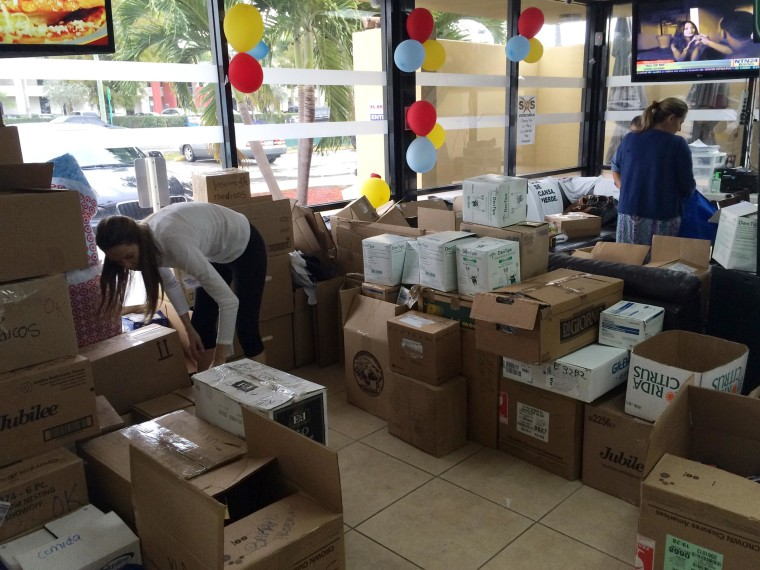"""Image: Medical supplies donations are packed for shipment at """"El Arepazo"""" restaurant in Doral, Fla."""