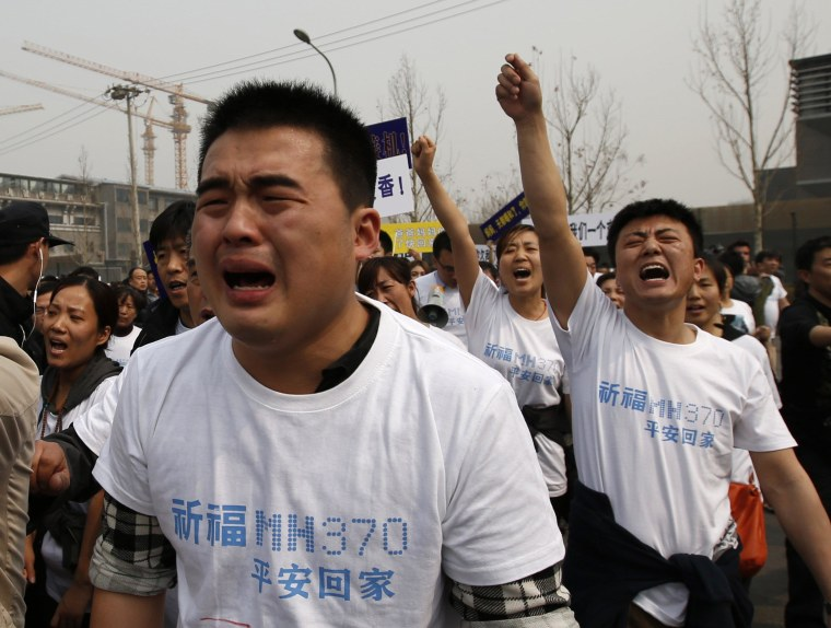 Image: Family members of passengers onboard Malaysia Airlines MH370 cry as they shout slogans during a protest in front of the Malaysian Embassy in Beijing
