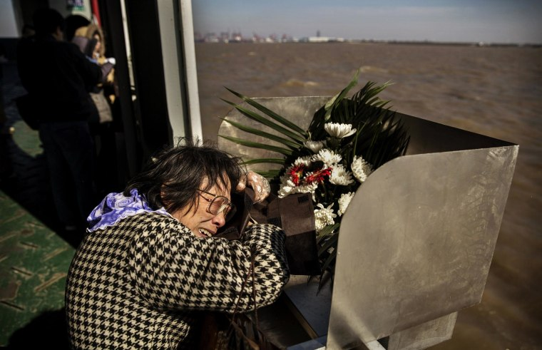 Image: Lin Hui Zhen, 76 years, weeps as she clutches the small bag carrying the ashes of her late husband Fu Yao Ming, 80 years, before placing them in a metal chute during a sea burial