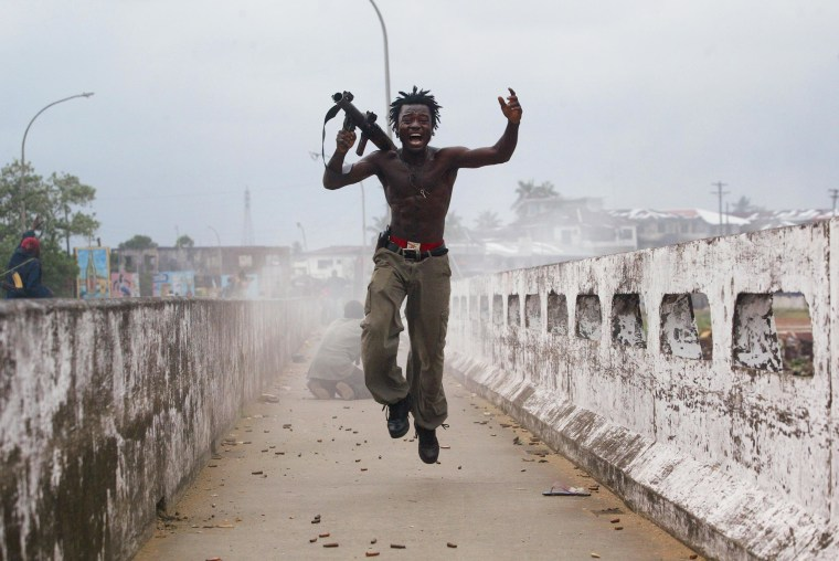Joseph Duo, a Liberian militia commander loyal to the government, exults after firing a rocket-propelled grenade at rebel forces at a key strategic bridge July 20, 2003 in Monrovia, Liberia. Government forces succeeded in forcing back rebel forces in fierce fighting on the edge of Monrovia's city center.
