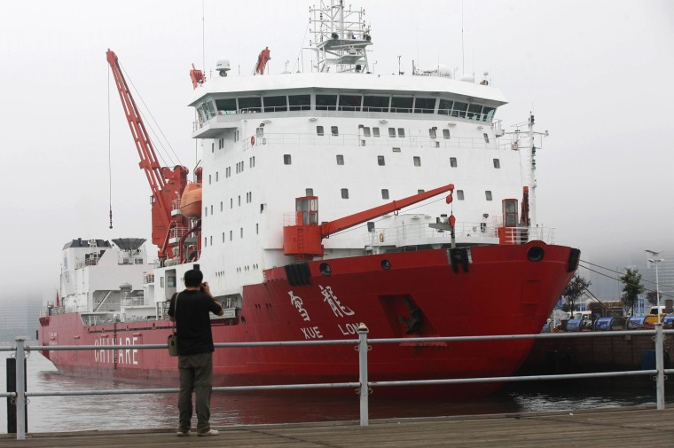 Image: A man takes a photo of Chinese icebreaker Xuelong