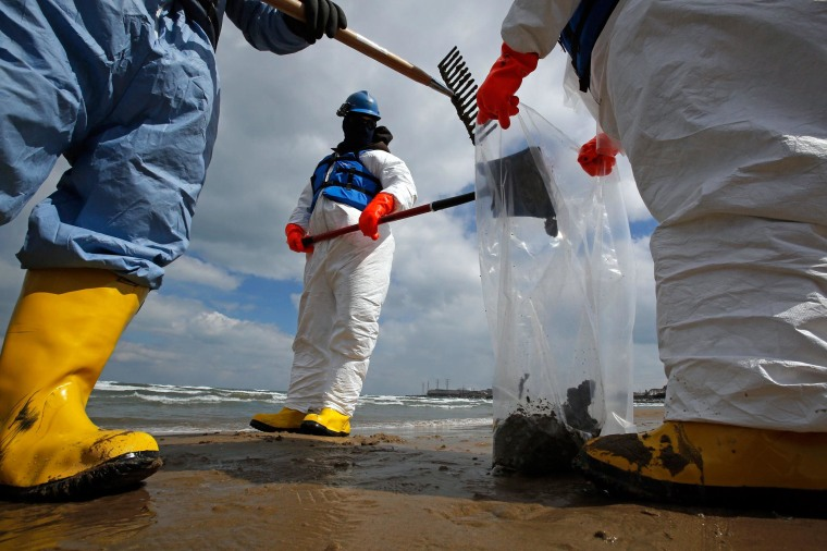 Image: Oil spill response contractors clean up crude oil on a beach after a BP oil spill on Lake Michigan in Whiting