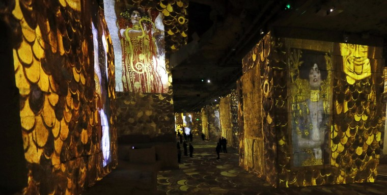 Visitors look at a sound and light show as part of the exhibition 'Klimt and Vienna, a Century of Gold and Colours', projected on the walls of the 'Carrieres de Lumieres' site (Quarries of Lights) in Les Baux-de-Provence, France on March 25.