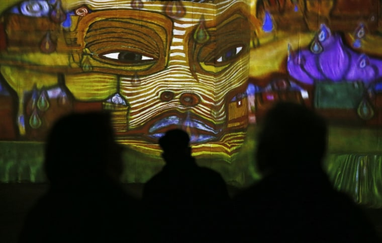 """Image: A visitor looks at a sound and light show as part of the exhibition 'Klimt and Vienna, a century of gold and colors', which projected on the walls of the """"Carrieres de Lumieres"""" site (Quarries of lights) in Les Baux-de-Provence"""