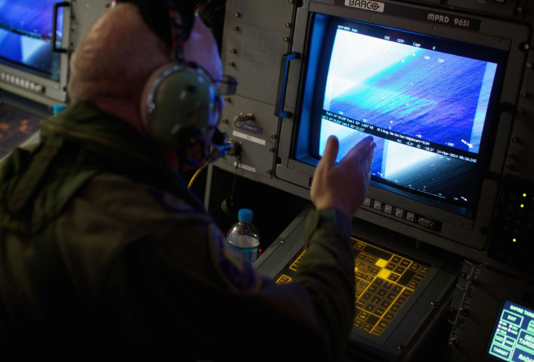 Image: A crewman of a RAAF AP-3C Orion aircraft looks at a screen while searching for missing Boein