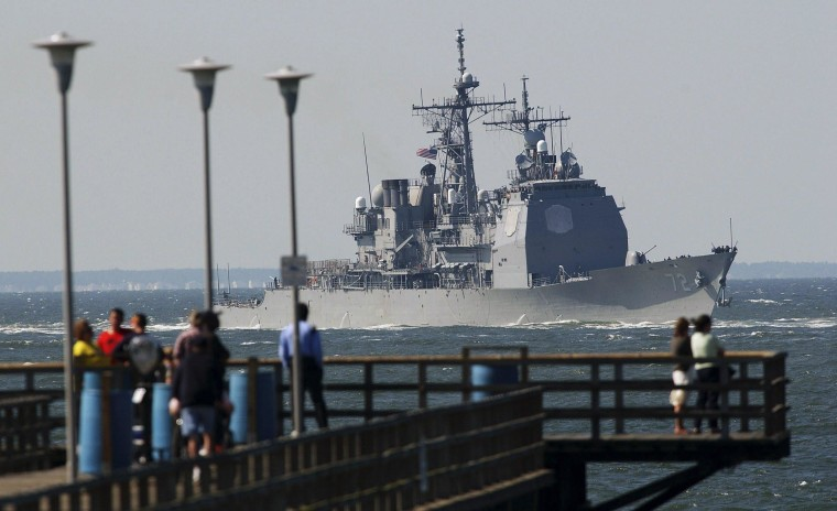 Image: Tourists watch the USS Mahan, an Arleigh Burke class destroyer, as it heads out to the Atlantic Ocean through the Chesapeake Bay-Bridge Tunnel complex near Virginia Beach in this file photo