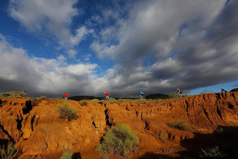 Image: Competitors ride through a dry river bed during the longest stage of the annual Absa Cape Epic mountain bike stage race near Cape Town, South Africa